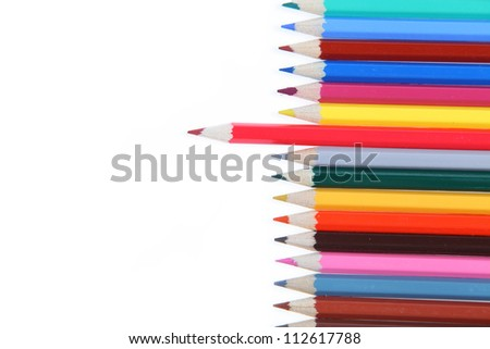 Many-colored pencils isolated on a white background. Red pencil pushed forward.