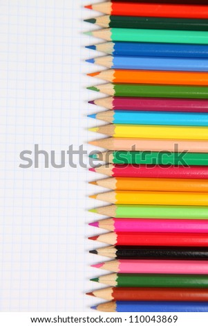 Many-colored pencils on a wooden table. Close-up.