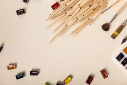 many colored pencils, watercolor paints and brushes are beautifully laid out on a light background, the view from above. The concept of creativity. High quality photo