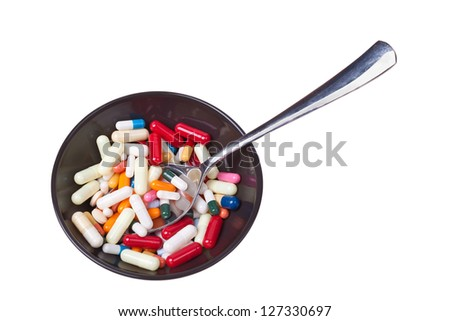 Many colored pills and capsules in a bowl with a spoon