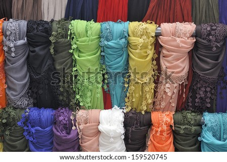 Many colored scarves on a display rack