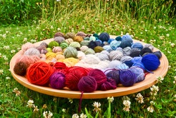 many colorful balls, clews, wads, ravels of wool, laying in a large wooden bowl standing on the ground of green grass