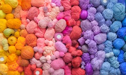 Many colorful balls of wool and cotton yarn for knitting. White background. Stretch and gradient. Rainbow layout.