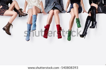 Many colorful boots series. Woman sitting on the white wall with various shoes.
