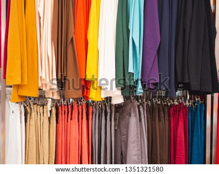 Many colorful cloth hanging on the clothes hanger in the clothing shop