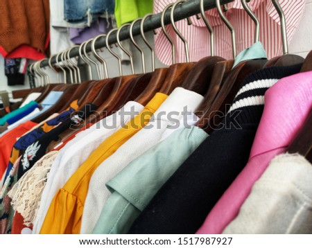 Many​ colorful​ clothes hang on​ clothes​ hangers on​ summer​ sale.
