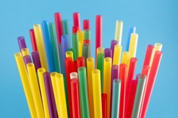 Many colorful drinking plastic straws above the blue color background, close-up