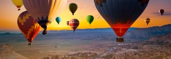 Many colorful hot air balloons flight above mountains - panorama of Cappadocia at sunrise. Wide landscape of Goreme valley in Cappadocia -  billboard background for your travel concept in Turkey.