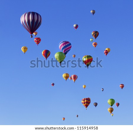Many colorful hot air balloons in blue sky at balloon fiesta