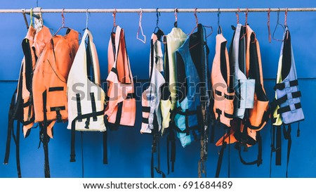 Many colorful life jacket or life vest hanging on a clothesline in front of the blue wall, equipment for safety in water transportation