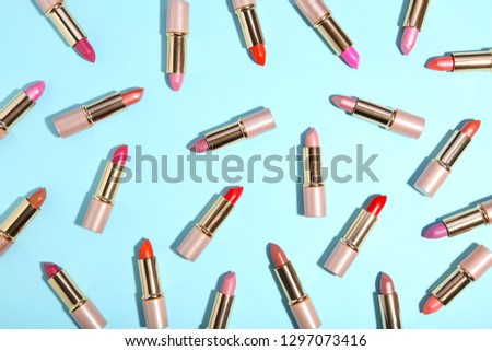 Many colorful lipstick on blue background. Cosmetic