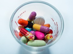 Many colorful pills in a cup of glass