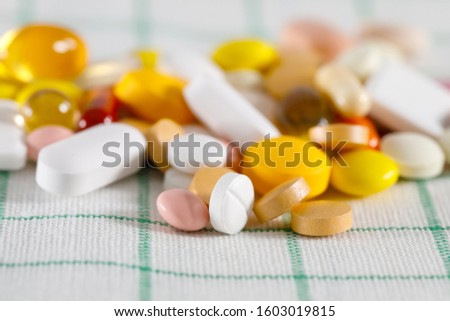 Many colorful pills on a napkin. These varied tablets have various shapes and various colors.