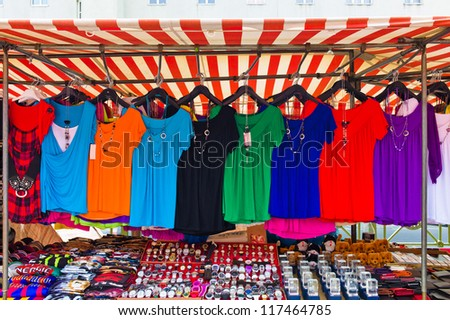 many colorful shirts for sale at a market entertainment. competition for textile trading