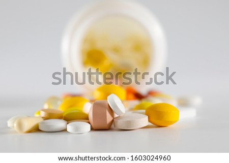 Many colorful tablets that fall out of a plastic bottle have various shapes and various colors.