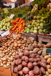 Many colorful vegetables: carrot, cucumber, pupkin, potato, zuccini - are aligned on selling place on farmers market