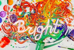 "Many colors are mixed on table: red, yellow, orange, blue, green, violet. The word ""Bright"" is written on paint. Paints, gouache and watercolors, brushes lie around. Creative concept of drawing, art."