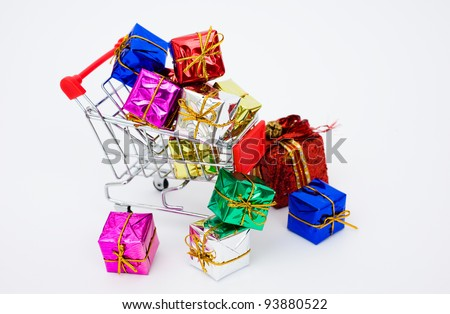 Many colors of christmas gifts in a shopping cart isolated on white background.