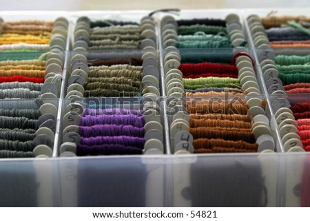 many colors of embrordary thread lined up in its  box on a white background