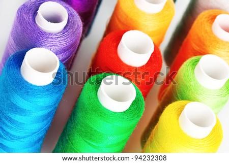 Many-coloured bobbins of thread closeup