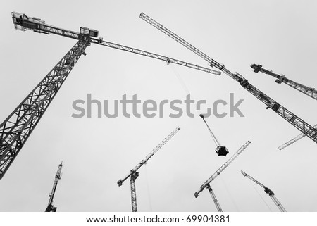 Many Construction crane against the sky and the houses under construction - stock photo