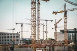 many cranes and construction workers on big construction site