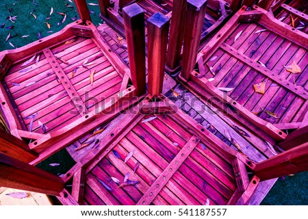 many crimson violet lilian vertical narrow strips with one horizontal plank with screws on wood joined into squares against autumn long leaves #541187557