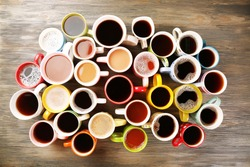 Many cups of coffee on wooden table, top view