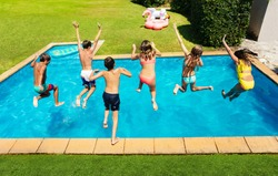 Many cute children jump into the swimming pool about to dive view from above