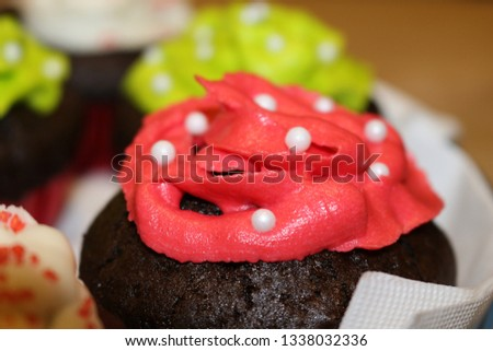 Many cute cupcakes in a plate. Different colorful icings. Green, pink and white icing with sparkles and candy.