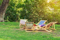 Many deck chairs and pillows with wooden table in the courtyard is surrounded by shady green grass. Comfortable pillows on outdoor patio chair and table in garden. Summer vacation. Selective focus.