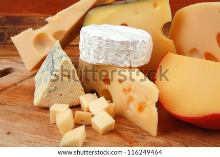 many delicious aged cheeses on wooden plate