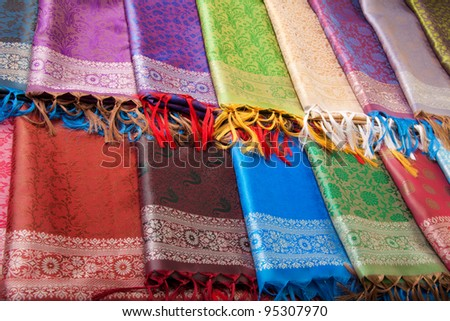 Many different color and texture fabrics on the table