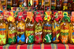 many different colored punch(rum and tropical fruits) bottles in a row on a typical market,guadeloupe, french west indies.