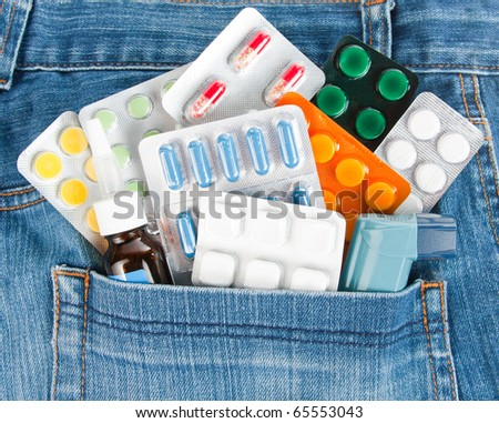 Many different colorful medicines in jeans pocket