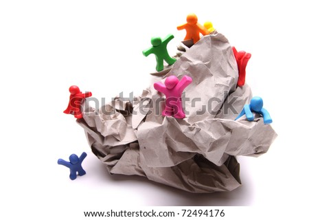 many different colorful plasticine guys climbing on a rock of paper - stock photo