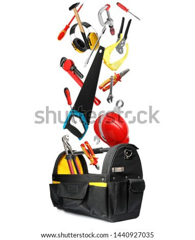 Many different construction tools falling into bag on white background