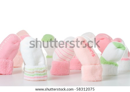 Many different green and pink socks for baby.