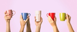 Many different hands holding multi colored cups of coffee on a pink background. Female and male hands. Concept of a friendly team, a coffee break, meeting friends, morning in the team. Banner