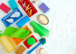 Many different household items. Cleanliness items on a white texture background. Household items of various kinds are arranged in a chaotic manner.