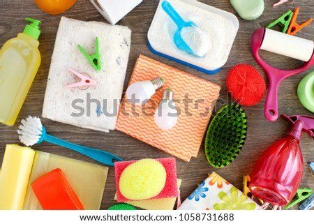Many different household items. Household items in the form of washing powder, garbage bags, bulbs, sprayer, washing liquid. View from above. home stuff are scattered on the table. #1058731688