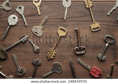 many different keys on wooden background concept