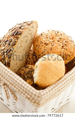 Many different kinds of bread in white basket.