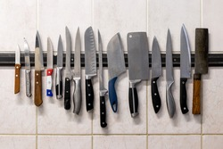 Many different knives are attached to a magnetic knife holder on the wall.
