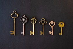 Many different old keys from different locks, in order in a line, flat lay. Finding the right key, encryption, concept. Retro vintage brass keys on a black background