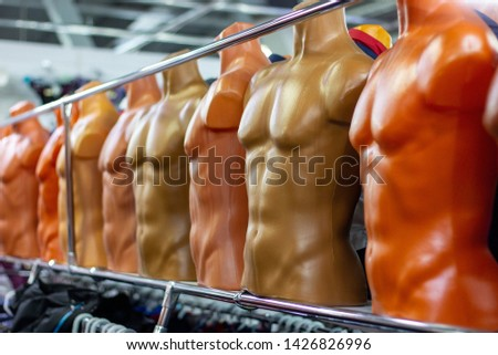 Many different plastic naked male mannequins in the clothing shop