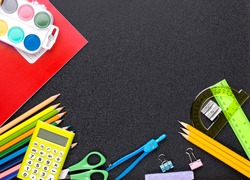 Many different school supplies on blackboard copy space background. Back to school concept.