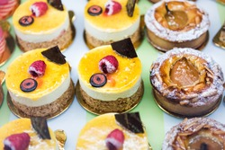 Many different selection variety of mini small cakes, pastries on display in bakery shop store with halloween cream decorations, raspberry tart