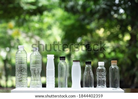 Many different shape drinking water bottles arrange into line with blur green garden background, re use container, eco friendly concept, copy space Foto stock ©