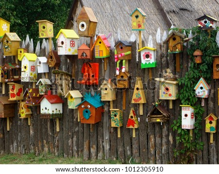 Many different shapes bird feeders birdhouse for nesting box hanging on wooden fence. Feeders for birds in city park. Colorful bird feeders in village. Lot of nesting boxes or houses for feeding birds